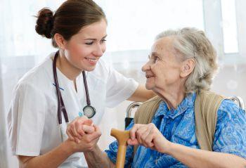 Alte Frau wird von jungen Pflegerin betreut
